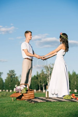beautiful wedding couple holding hands on picnic