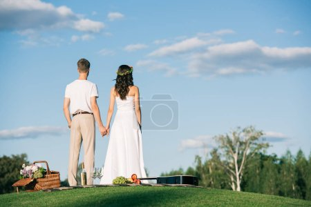 back view of wedding couple holding hands on lawn with picnic