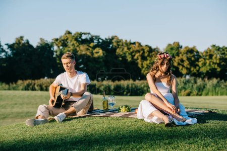groom playing guitar for upset bride during romantic picnic on lawn