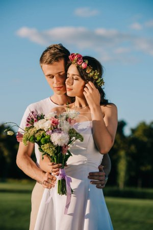 groom embracing his attractive bride in flower wreath with wedding bouquet
