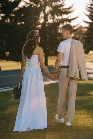 back view of attractive bride and handsome groom holding hands outdoors