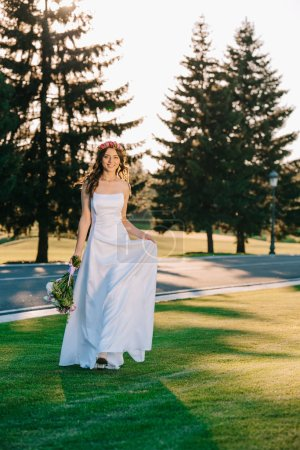 beautiful happy young bride holding wedding bouquet and smiling at camera in park