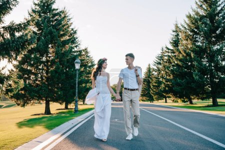 beautiful happy young wedding couple holding hands and smiling each other while walking together in park