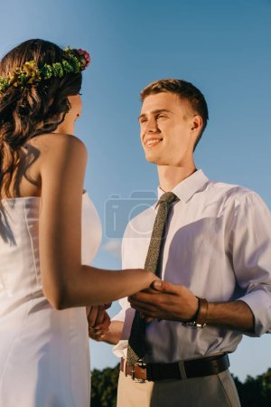 low angle view of happy young wedding couple holding hands and smiling each other against blue sky