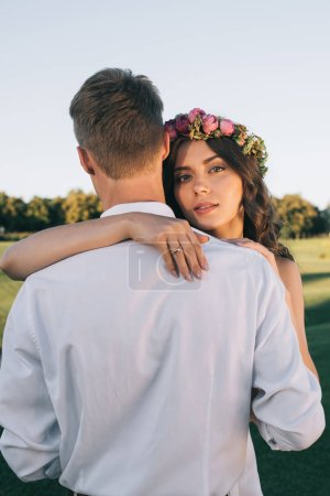 attractive young bride in floral wreath hugging groom and looking at camera in park