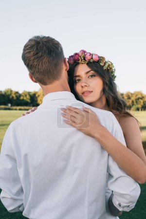 beautiful young bride in floral wreath hugging with groom and looking at camera in park