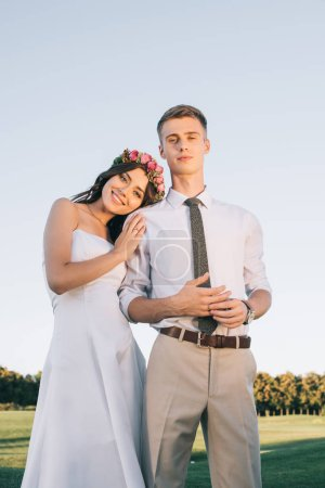 low angle view of beautiful young wedding couple standing together and smiling at camera in park