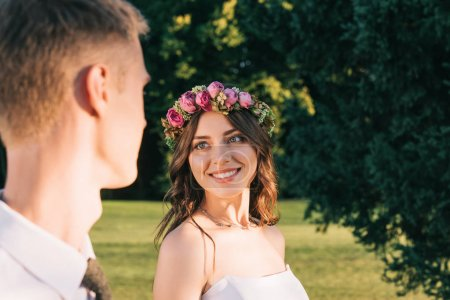 cropped shot of beautiful happy young bride and groom smiling each other in park