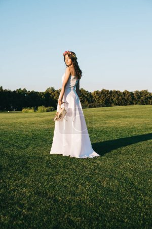 beautiful young bride holding shoes and looking at camera while standing on green lawn
