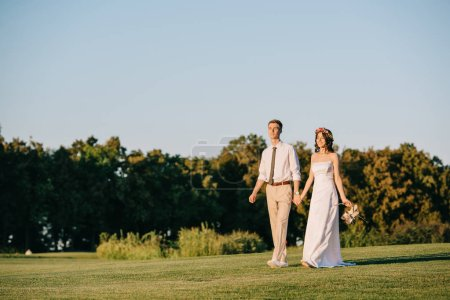 beautiful happy young wedding couple holding hands and walking together in park