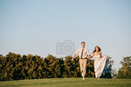 happy young wedding couple running on green meadow in park