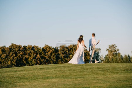 back view of beautiful young wedding couple walking on green meadow in park