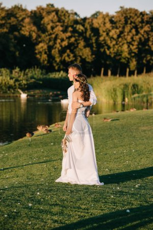 beautiful happy young wedding couple embracing while standing near lake in park