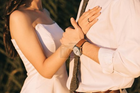 cropped shot of loving young wedding couple embracing and holding hands