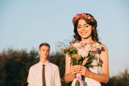 beautiful happy young bride holding wedding bouquet and groom standing behind