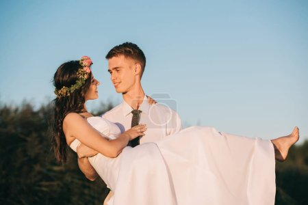 happy young groom carrying beautiful bride against blue sky
