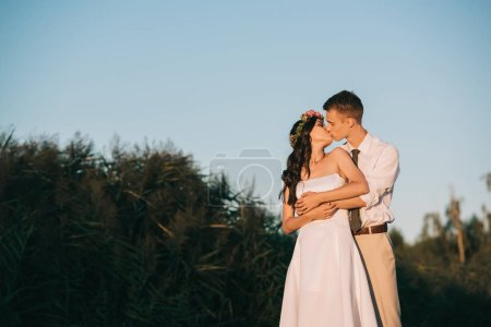 beautiful elegant young wedding couple kissing in park