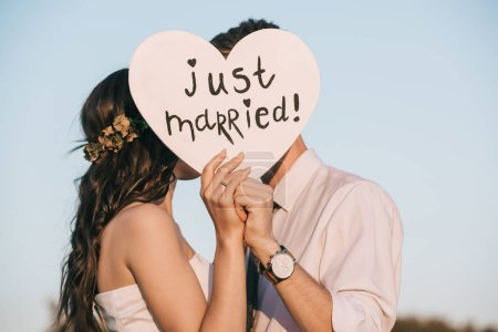 young wedding couple kissing and holding heart with just married inscription