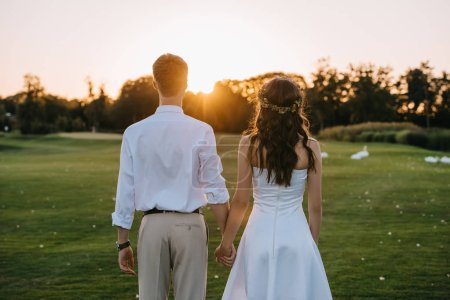 back view of young wedding couple holding hands and standing together in park at sunset