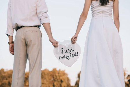 cropped shot of young wedding couple holding heart with just married inscription