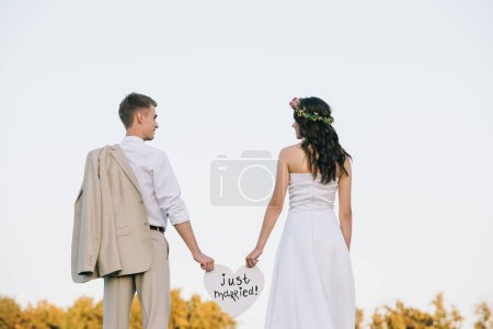 Photo pour Vue arrière du jeune couple de mariage tenant le coeur avec l'inscription juste mariée - image libre de droit