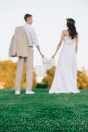 selective focus of young wedding couple standing together on green lawn