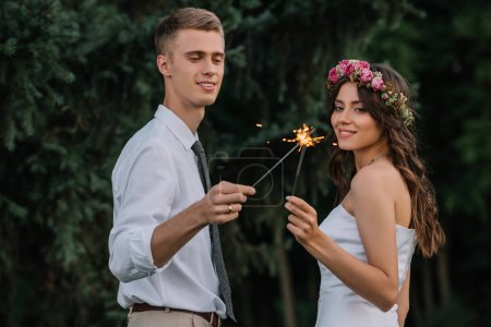 beautiful happy young wedding couple holding sparklers outdoors