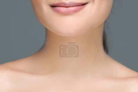 partial view of smiling woman with bare shoulders isolated on grey