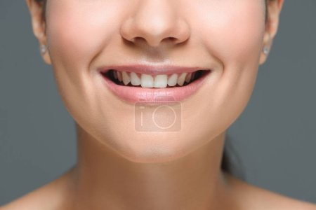 partial view of smiling woman with beautiful white teeth isolated on grey