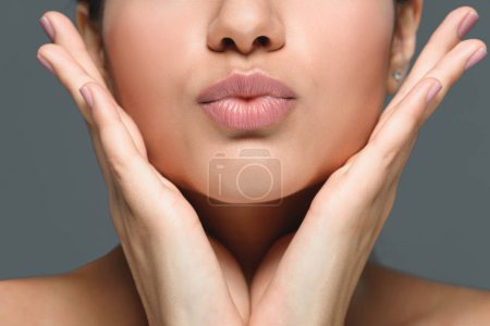 partial view of woman with hands at cheeks and duck face isolated on grey