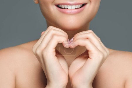 cropped shot of smiling woman with white teeth showing heart sign with hands isolated on grey