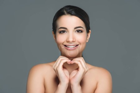 Photo for Portrait of beautiful smiling woman with white teeth showing heart sign with hands isolated on grey - Royalty Free Image