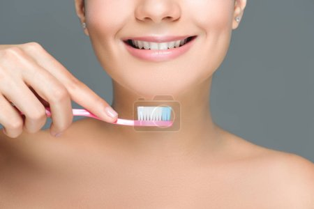 Photo for Cropped shot of smiling woman holding tooth brush in hand isolated on white - Royalty Free Image