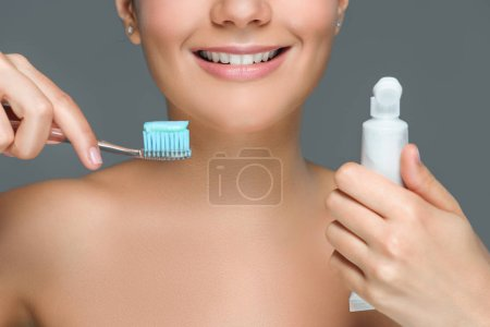 partial view of smiling woman with tooth brush and tooth paste tube in hands isolated on grey