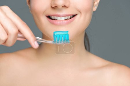 cropped shot of smiling woman holding tooth brush with tooth paste isolated on grey