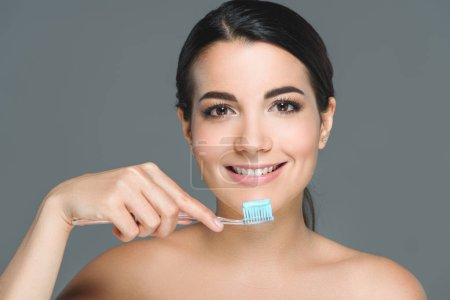 Photo for Portrait of of smiling woman holding tooth brush with tooth paste isolated on grey - Royalty Free Image