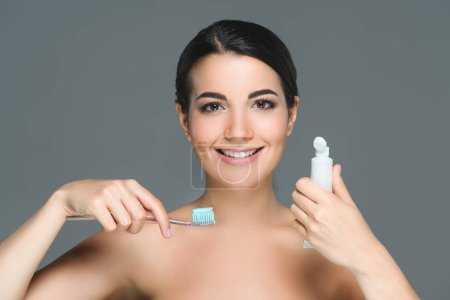 Photo for Portrait of smiling woman with tooth brush and tooth paste tube in hands isolated on grey - Royalty Free Image