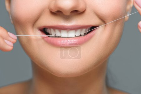 partial view of smiling woman with beautiful white teeth and dental floss isolated on grey