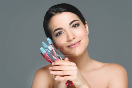 portrait of beautiful woman holding tooth brushes isolated on grey