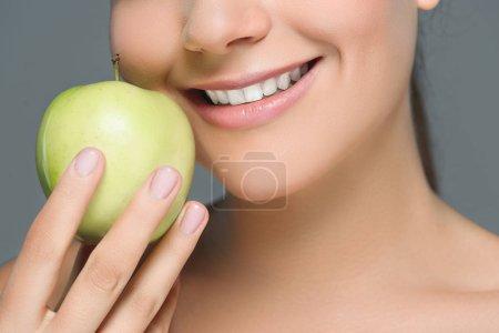 Photo pour Vue partielle de la femme aux dents blanches et pomme fraîche isolée sur gris - image libre de droit