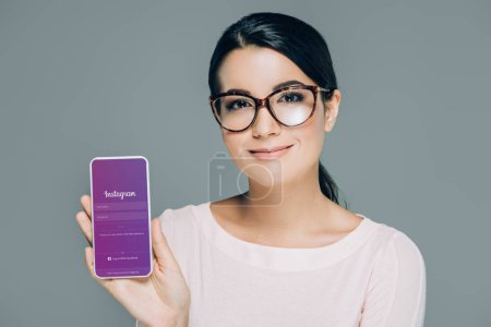 Photo for Portrait of smiling woman in eyeglasses showing smartphone with instagram app on screen isolated on grey - Royalty Free Image