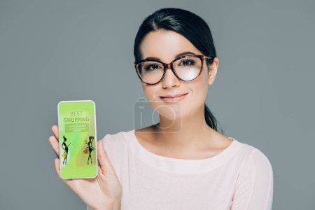 portrait of smiling woman in eyeglasses showing smartphone with best shopping website on screen isolated on grey
