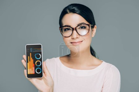 portrait of smiling woman in eyeglasses showing smartphone with graphics on screen isolated on grey