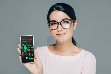 Photo for Portrait of smiling woman in eyeglasses showing smartphone with marketing analysis on screen isolated on grey - Royalty Free Image