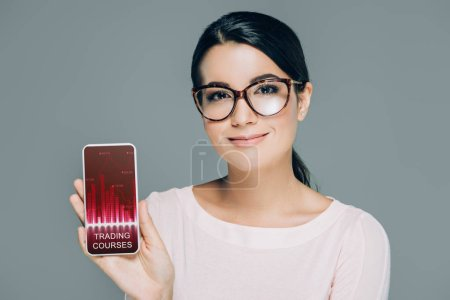 portrait of smiling woman in eyeglasses showing smartphone with trading courses logo on screen isolated on grey
