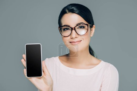 portrait of beautiful brunette woman in eyeglasses showing smartphone with blank screen in hand isolated on white