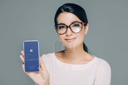 portrait of smiling woman in eyeglasses showing smartphone with facebook logo on screen isolated on grey