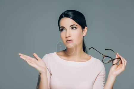 portrait of beautiful brunette woman with eyeglasses gesturing isolated on grey