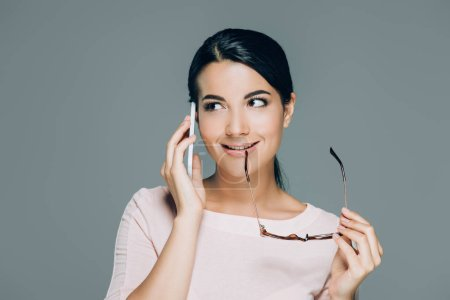 portrait o beautiful brunette woman with eyeglasses talking on smartphone isolated on grey