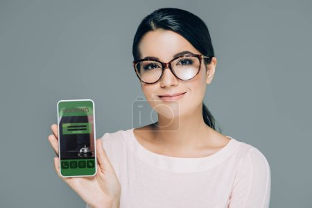 portrait of smiling woman in eyeglasses showing smartphone with booking website on screen isolated on grey